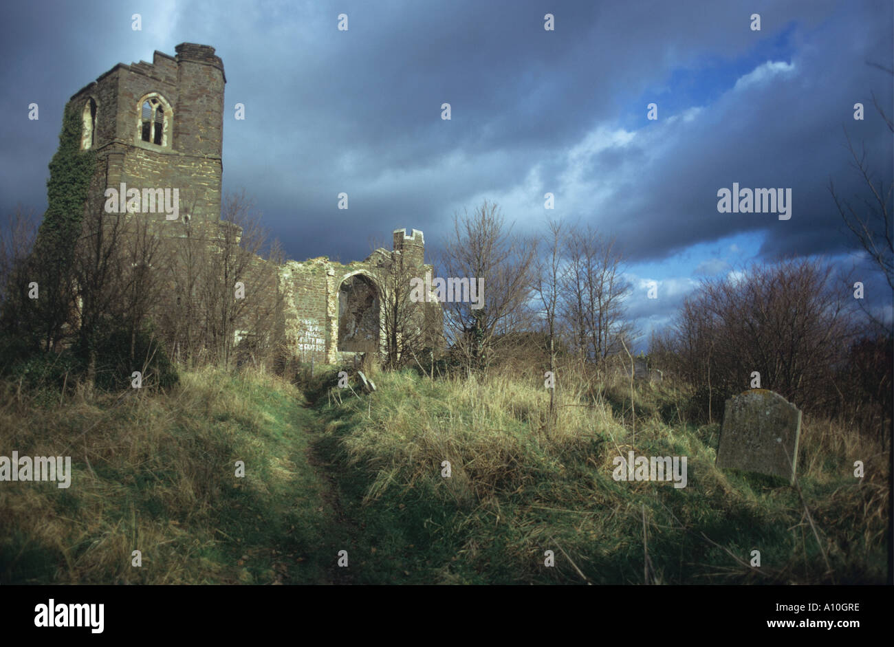 Ruins of church on a hilltop above Clophill East of Ampthill Bedfordshire Graffiti on walls and desecrated graves - Stock Image