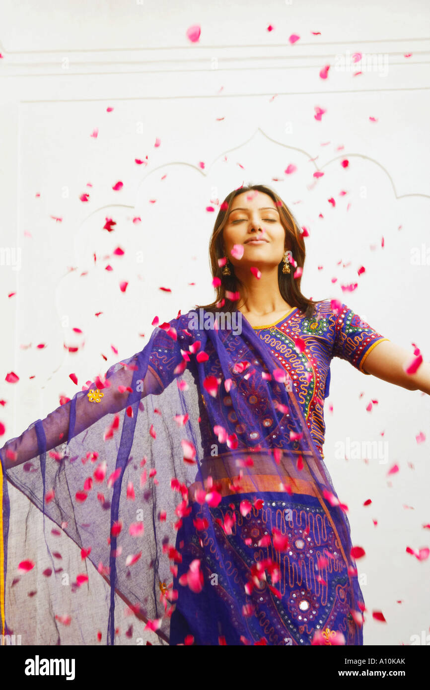 Close-up of a young woman standing with rose petals falling around her - Stock Image