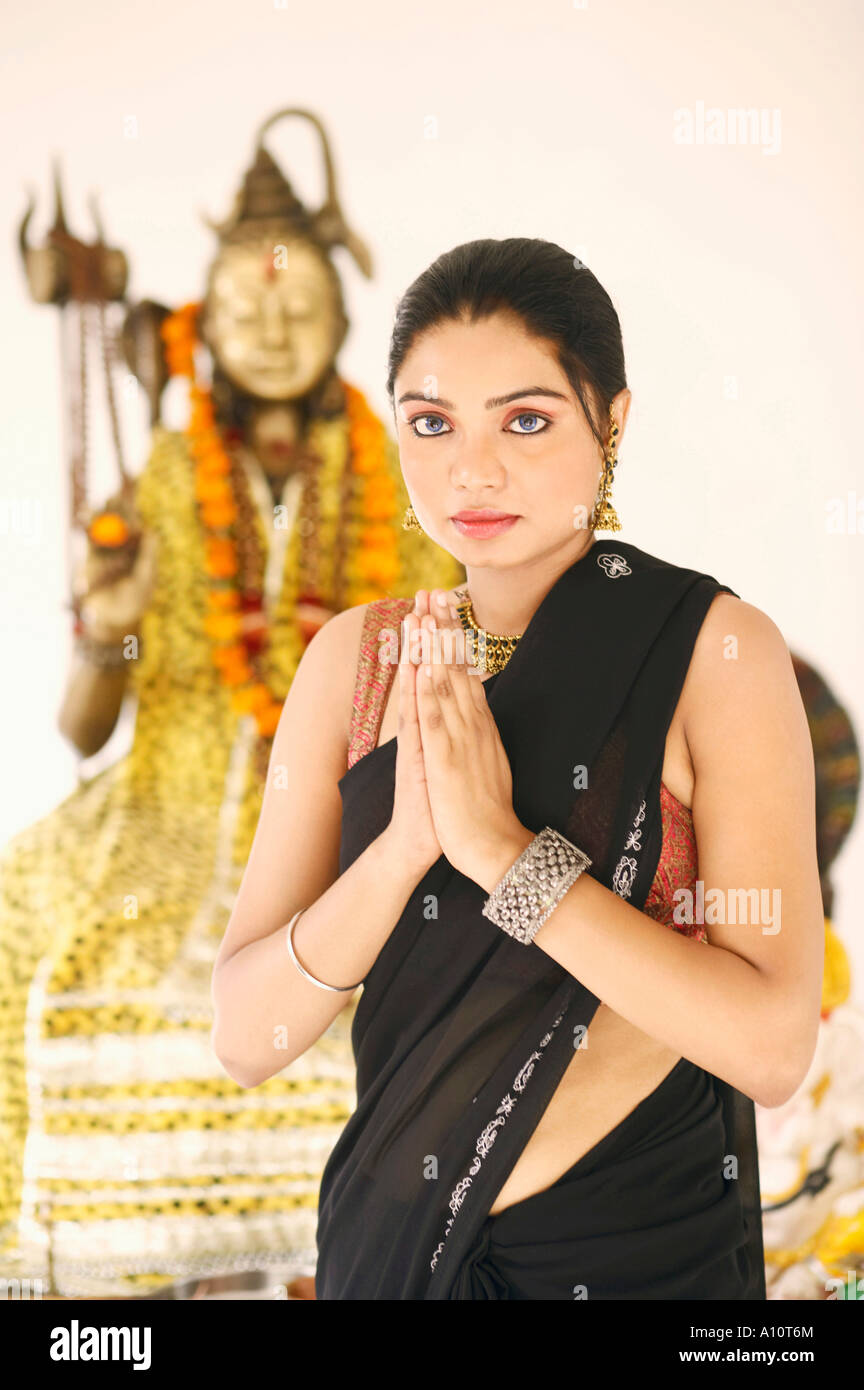 Portrait of a young woman standing in a prayer position in front of an idol of Lord Shiva - Stock Image