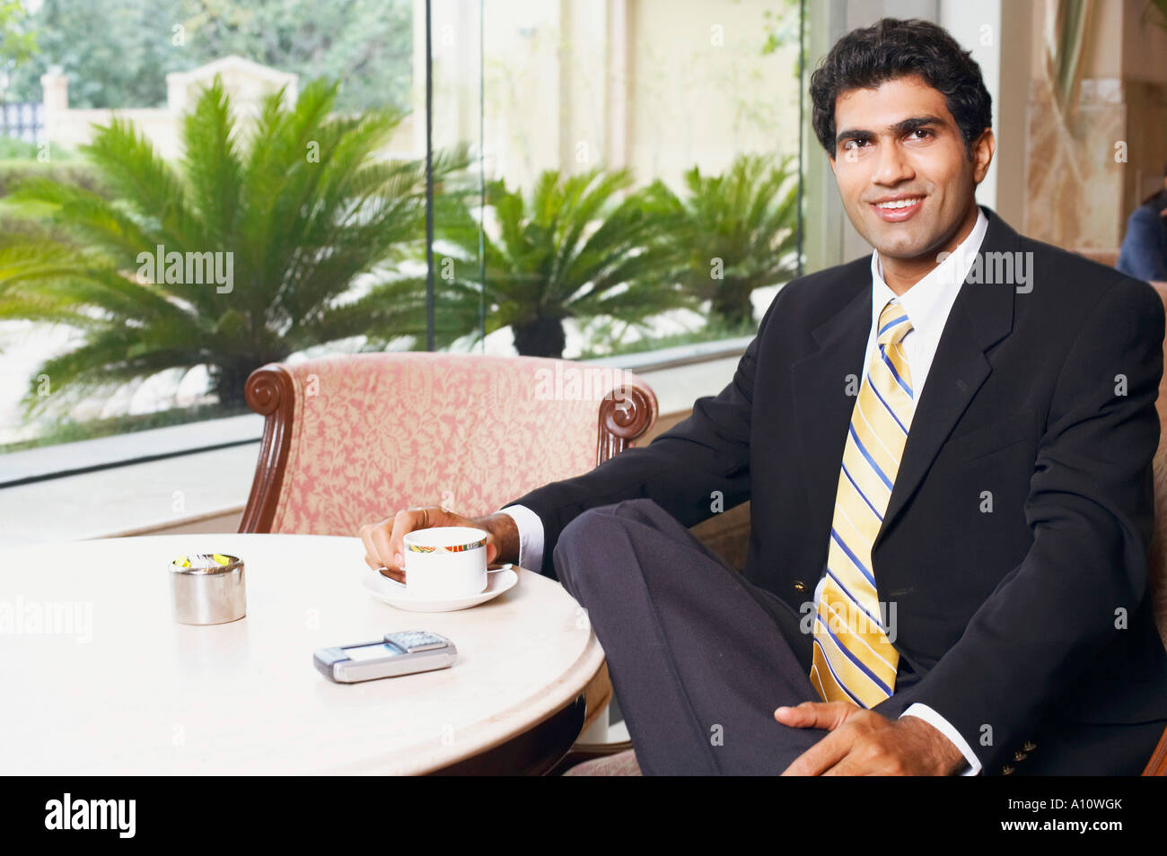 Close-up of a businessman sitting in a cafeteria - Stock Image