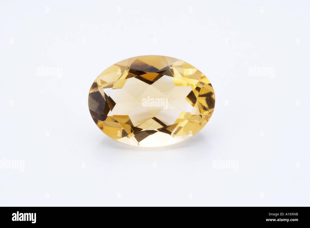 One single piece of oval shaped shining glittering star warm yellowish coloured Citrine Semi Precious Stone on white background - Stock Image