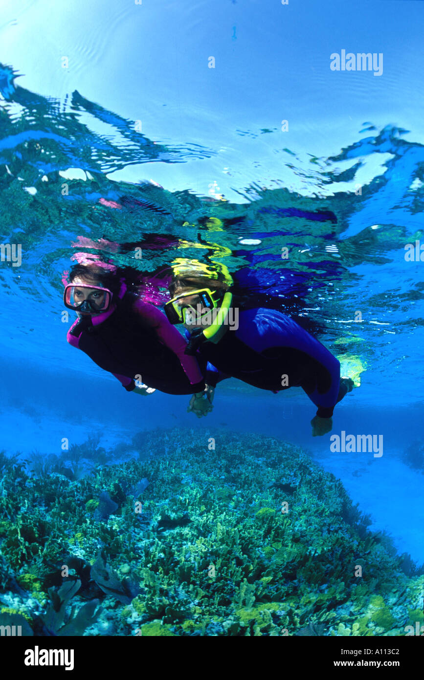 A COUPLE IN BRIGHTLY COLORED SNORKEL EQUIPMENT SWIM OVER A HEALTHY REEF IN THE CLEAR WATERS OF THE BAHAMAS - Stock Image
