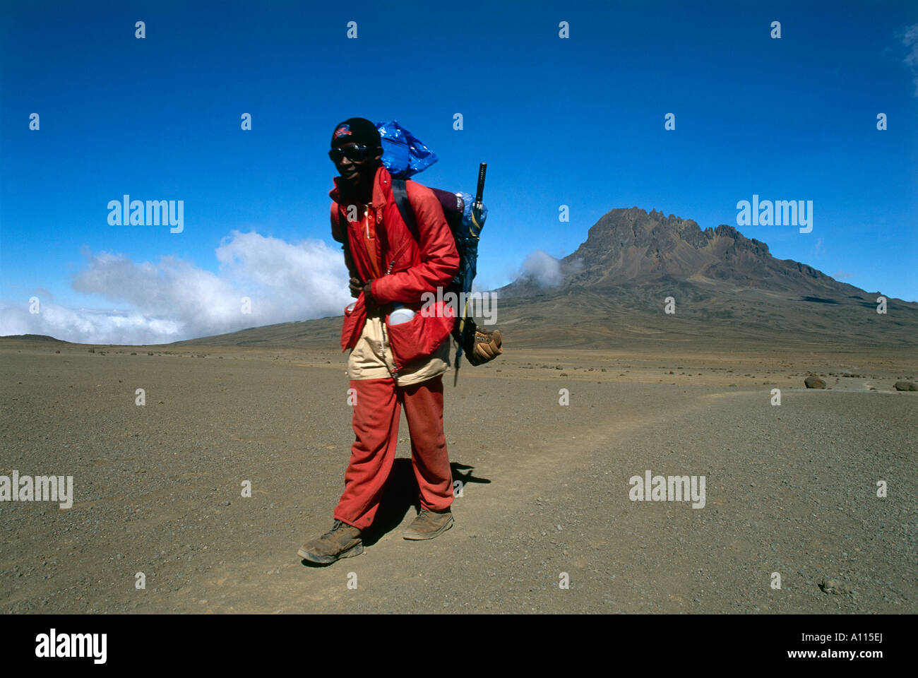 A local guide Nelson Mongi treks across The Saddle at 4 400m one of the peaks of Kilimanjaro with Mawenzi Peak in - Stock Image