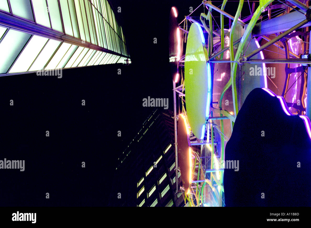 Dynamic  modern structures looking up to black sky and coloured lights - Stock Image
