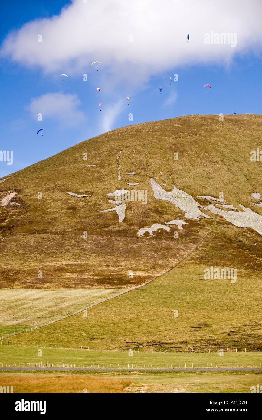 A flock of paragliders over a hill (Puy de Dôme - France). Parapentistes au-dessus d'une colline (Puy-de - Stock Image