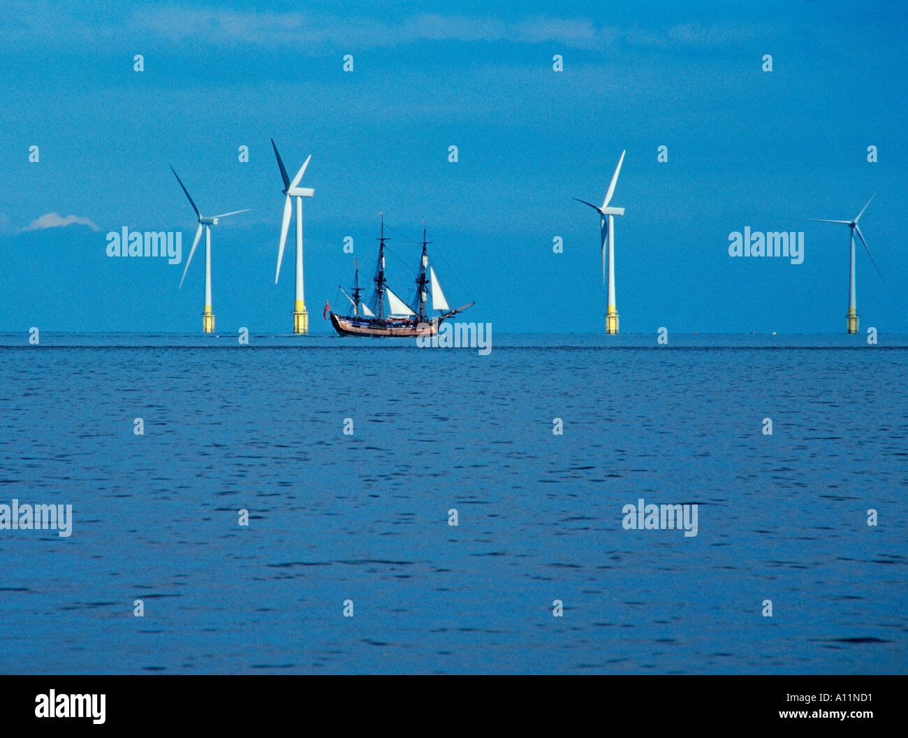 17th Century sailing ship sails past 21st century offshore wind farm - Stock Image