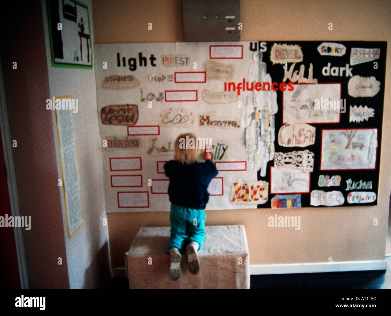 small blond boy looking at a collage wall in a school room - Stock Image