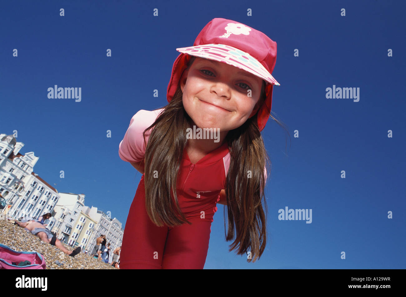 Ten year old girl plays in pink uv sunsuit on Brighton Beach Sussex UK - Stock Image