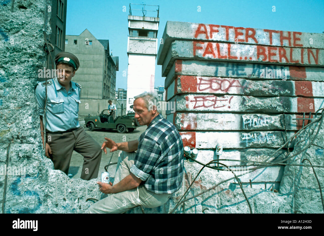 (Former East) Berlin Germany, GDR East German Border Guard at 'Berlin Wall' Looking through Wall, Talking to Man (Vintage Photo) - Stock Image