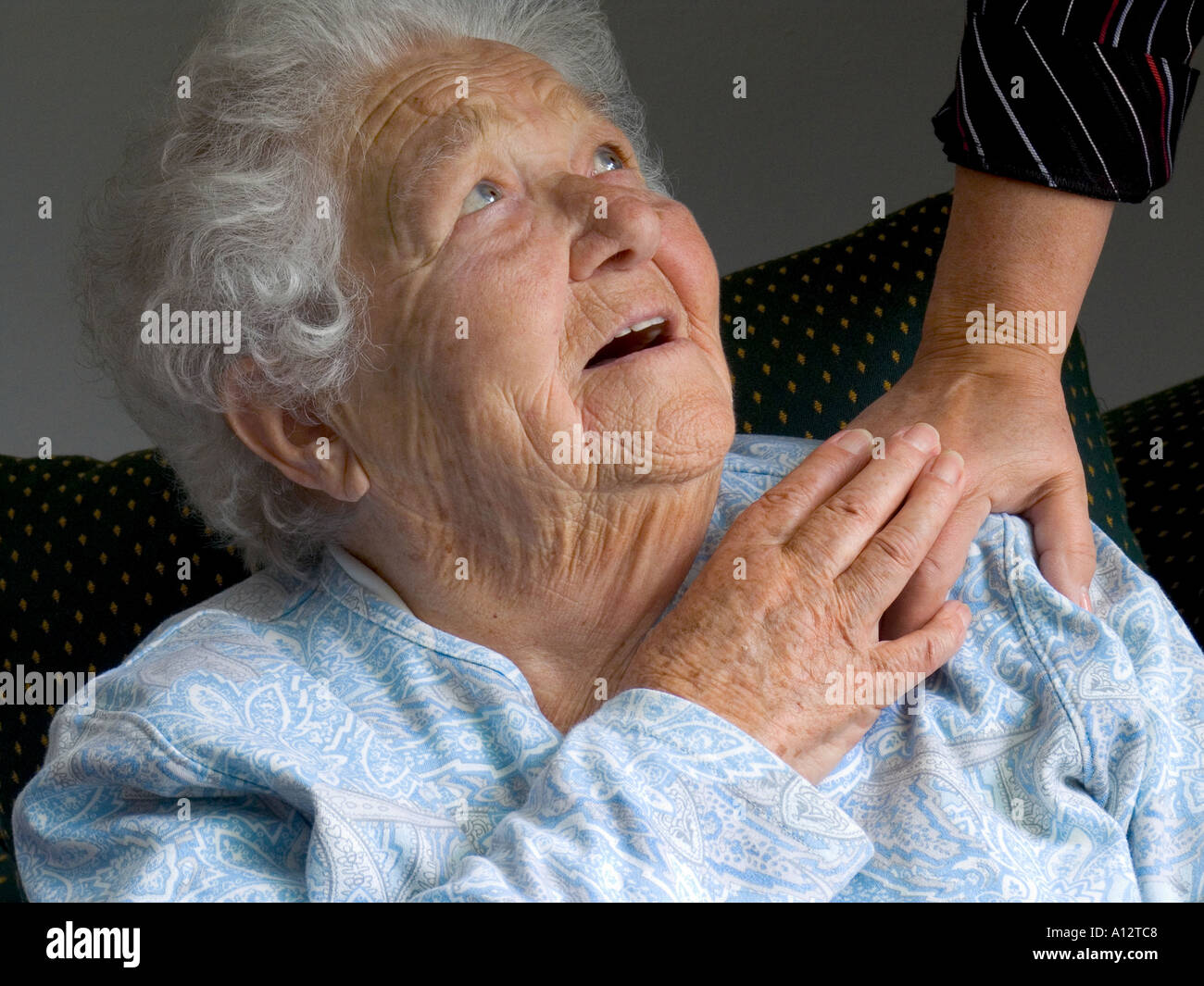 Contented smiling senior old age elderly woman looks up and touches comforting hand of carer - Stock Image