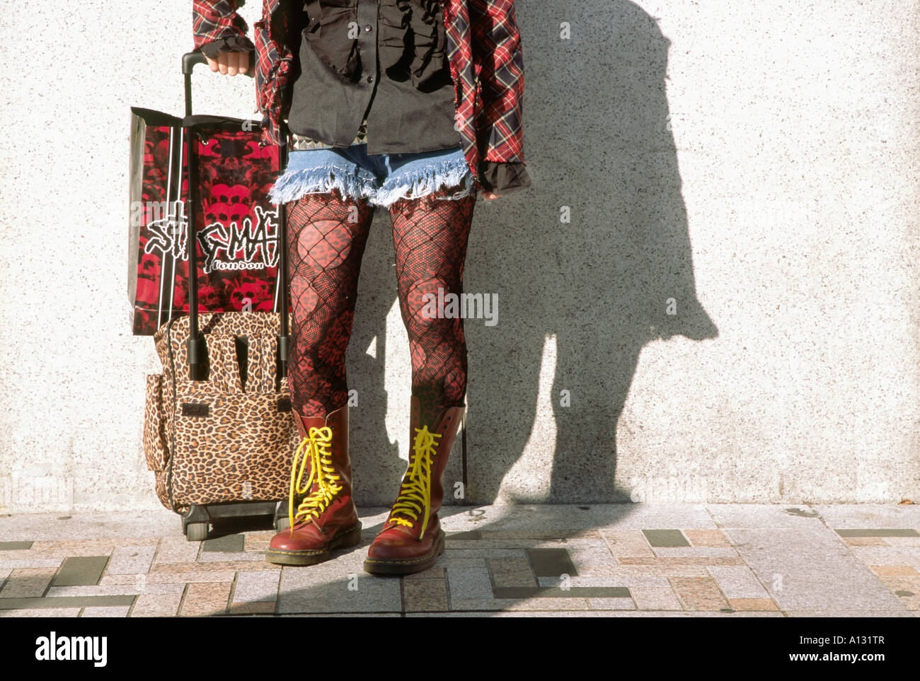 Detail of a cos-player's legs with a wheely bag. Harajuku, Tokyo, Japan - Stock Image
