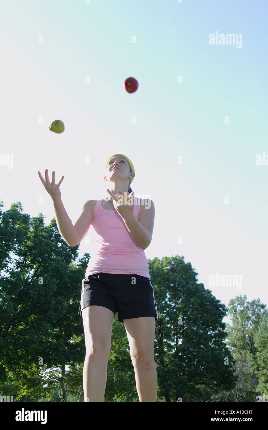 Caucasian girl juggle fruits on the field - Stock Image