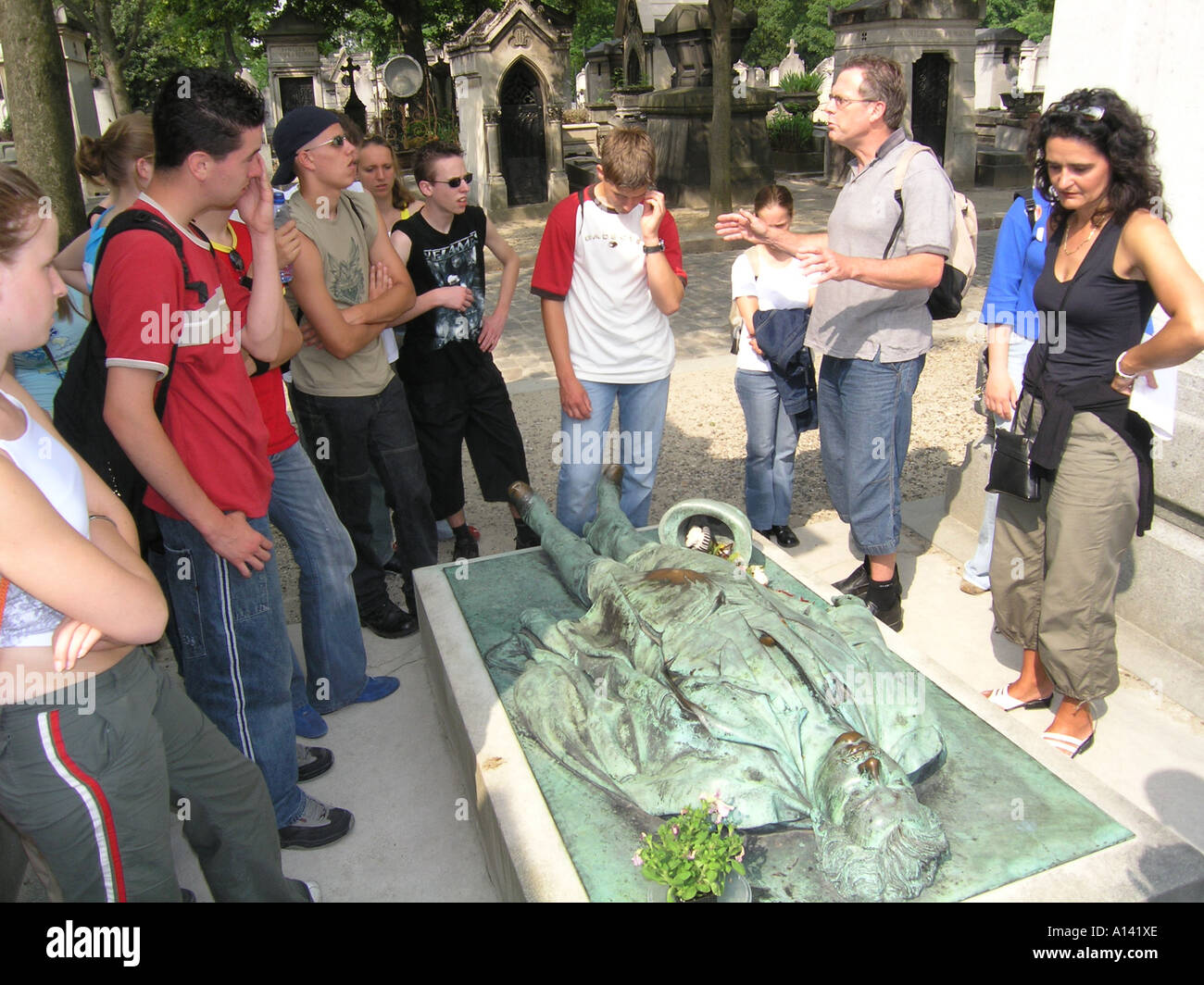 school group visiting grave of Victor Noir at Pere Lachaise cemetery Paris France - Stock Image