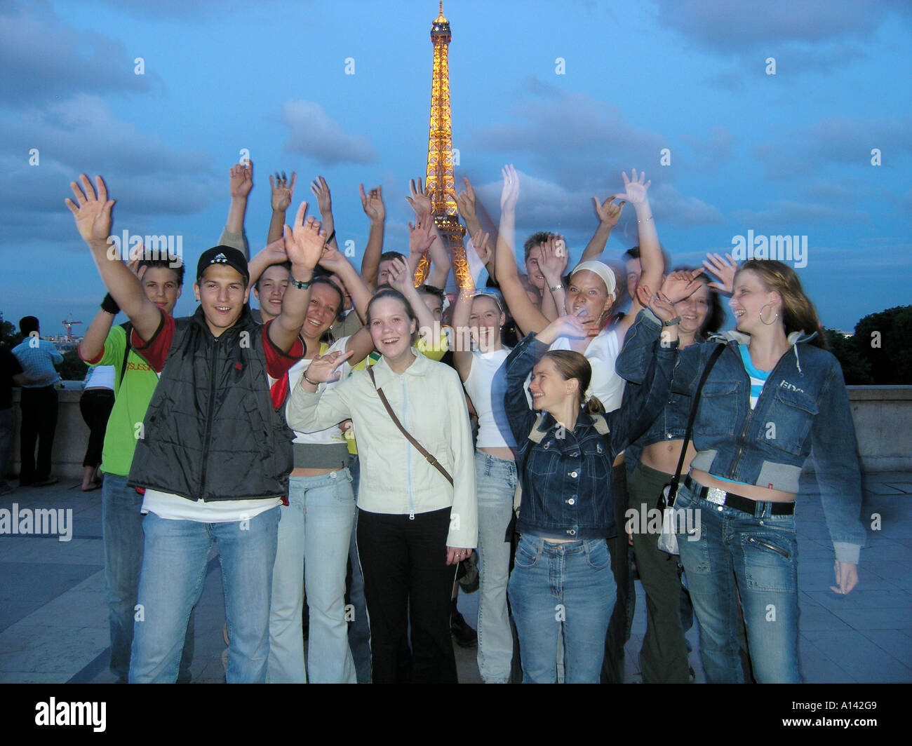 snapshot of teenage school group waving at the camera in front of Eiffel Tower at dusk Paris France - Stock Image