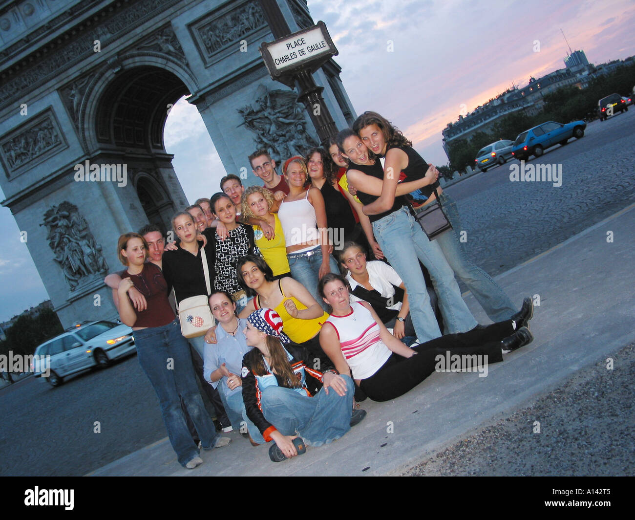 school group of young adults posing in front of Arc de Triomphe Paris France at dusk - Stock Image