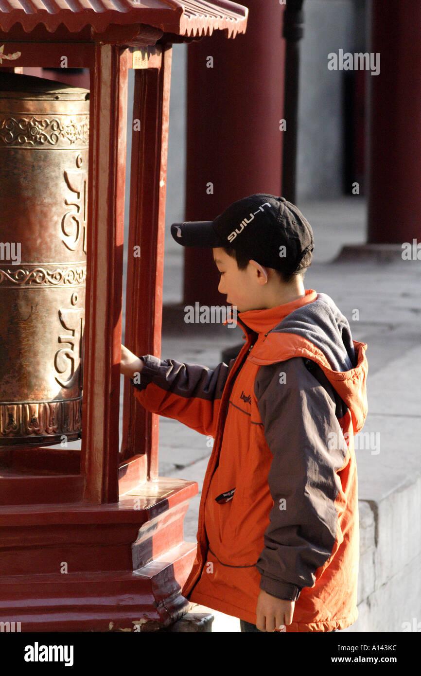 Boy spins a prayer wheel at the Lama Temple, Dongcheng, Beijing,  China - Stock Image