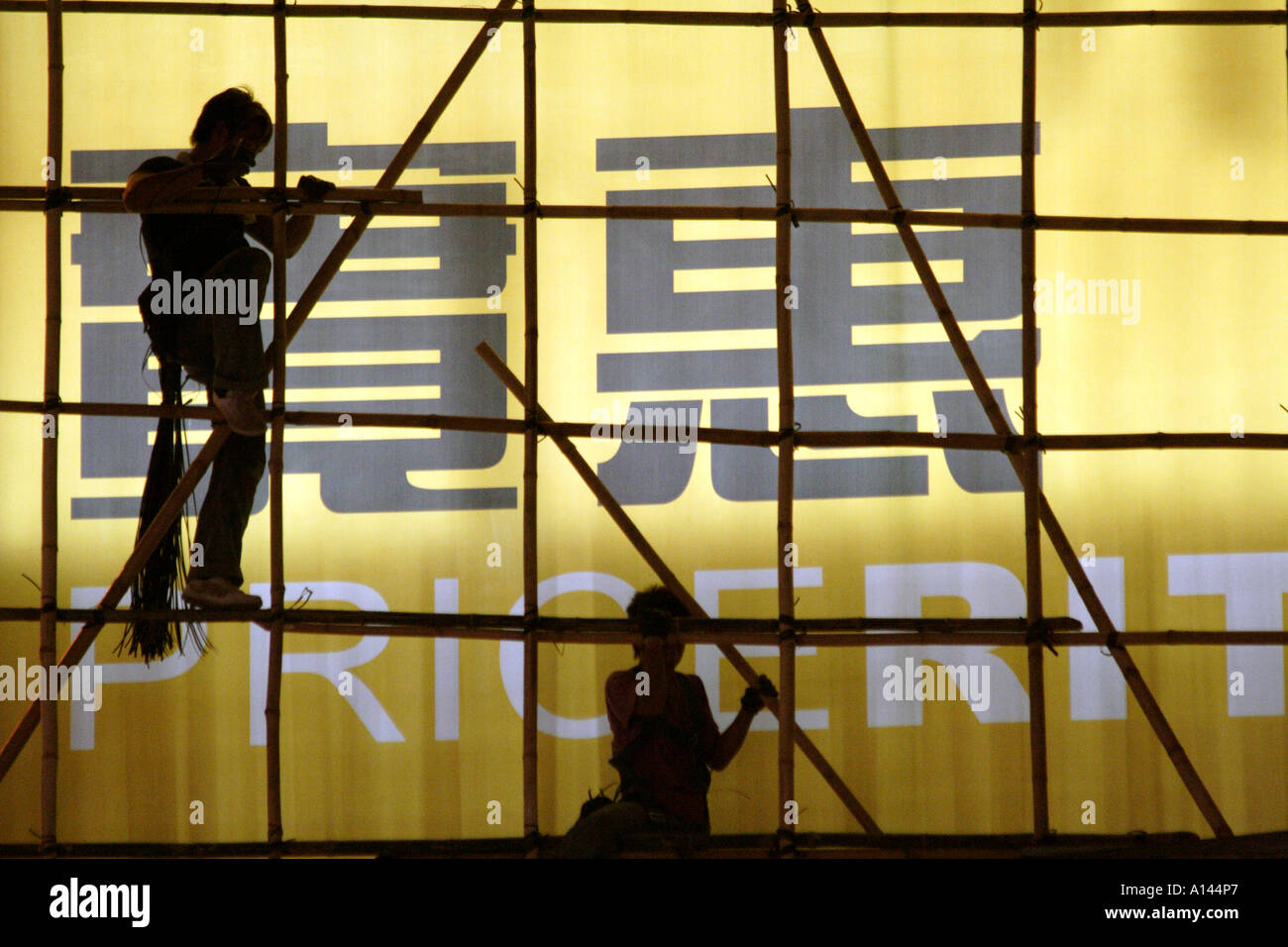 Workers place bamboo poles to create a scaffolding in Mongkok, Kowloon, Hong Kong SAR - Stock Image