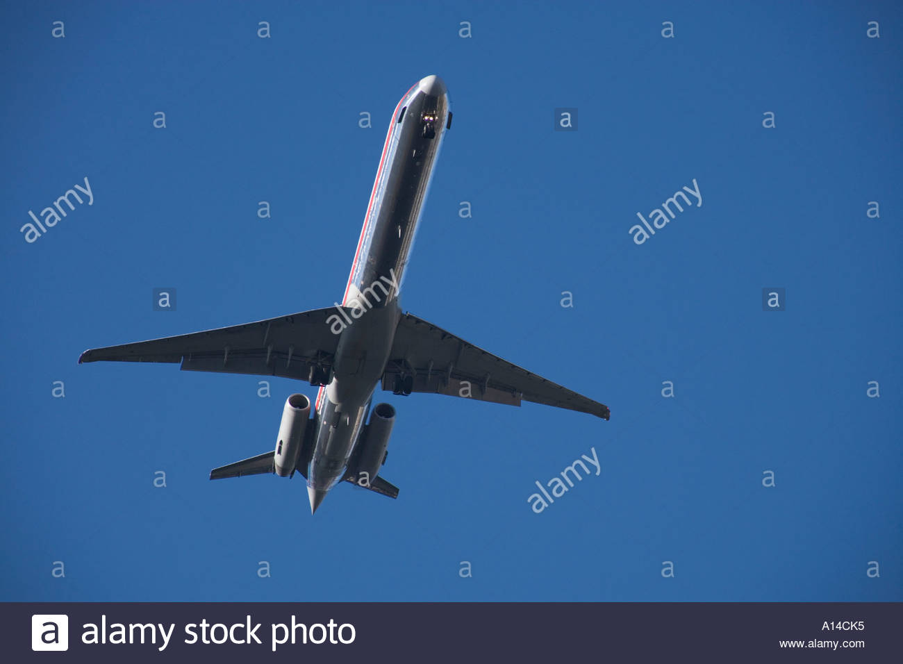silhouette of an airplane flying low - Stock Image