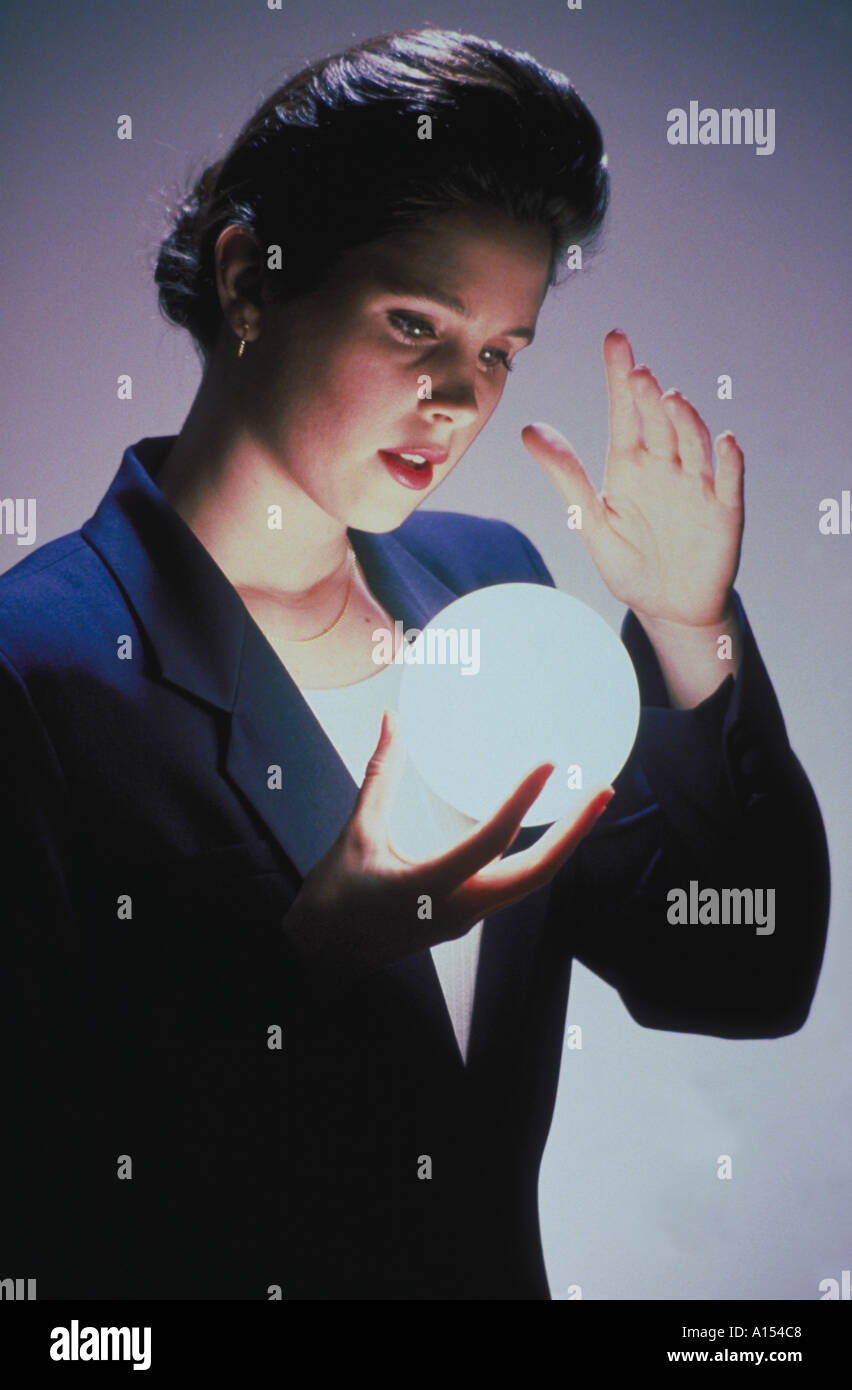 A business woman gazes into a glowing ball that she is holding as if to see the future - Stock Image