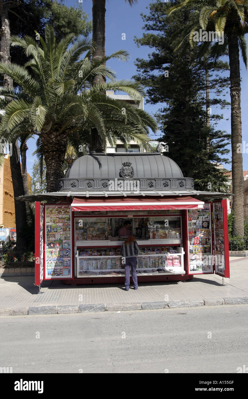 Making a purchase from a cast iron news kiosk on the roadside in Cartagena Spain - Stock Image