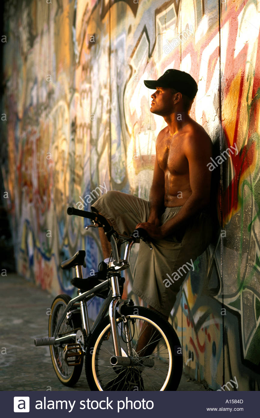 BMX Flatland Freestyle Bike bicycle rider standing with graffiti on wall Venice Beach California - Stock Image