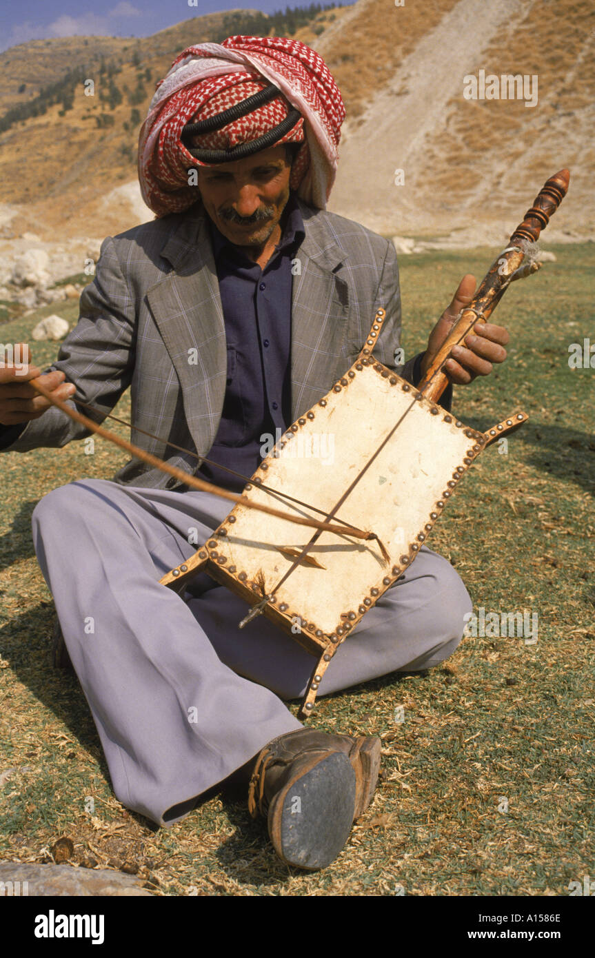 Musician wearing traditional headcloth playing the rabala a traditional single string instrument Jordan Middle East K Gillham - Stock Image