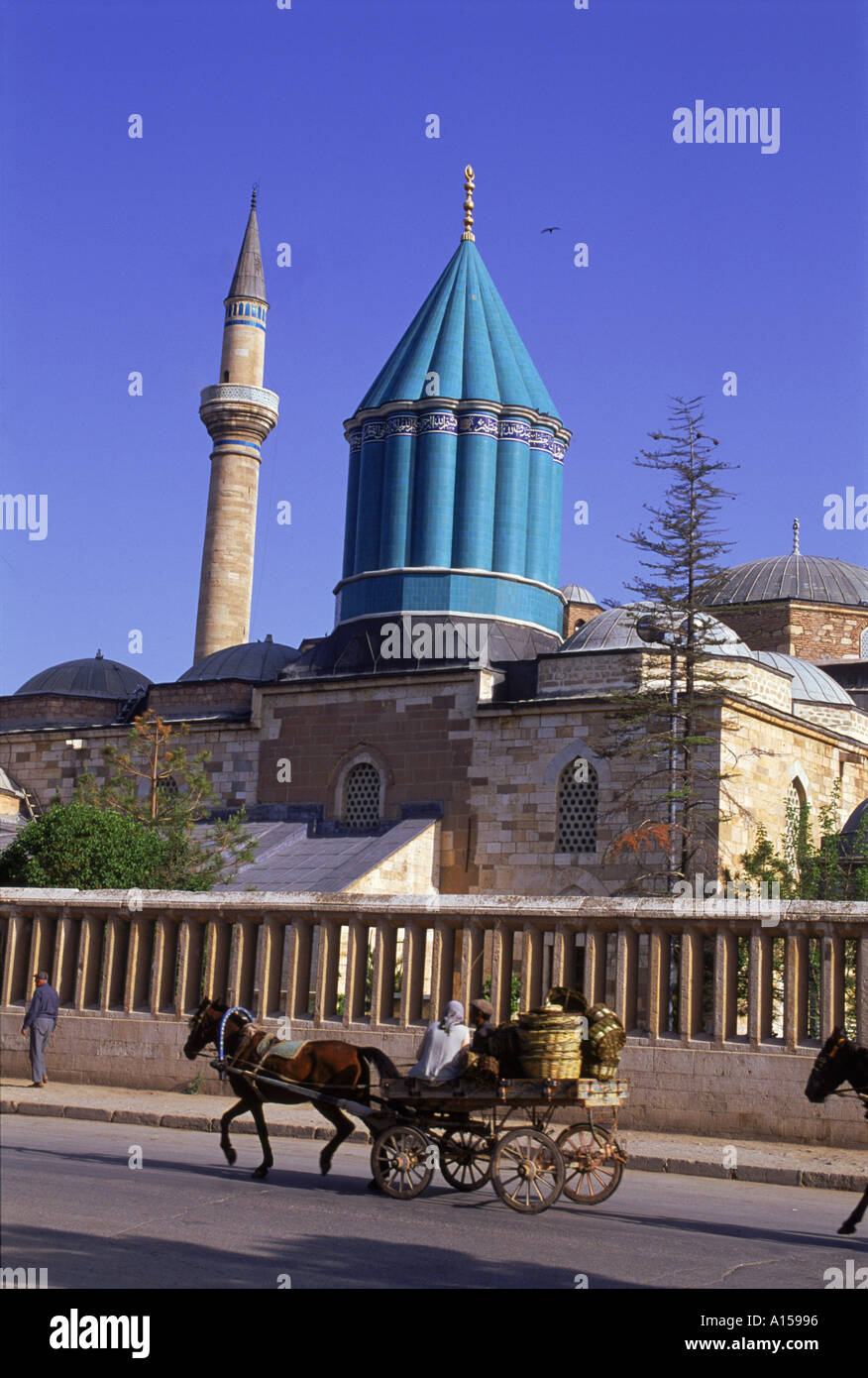 Horse and cart passes the Mevlana Tekke Museum with its green tower and minaret formerly the monastery or tekke of the Whirling - Stock Image