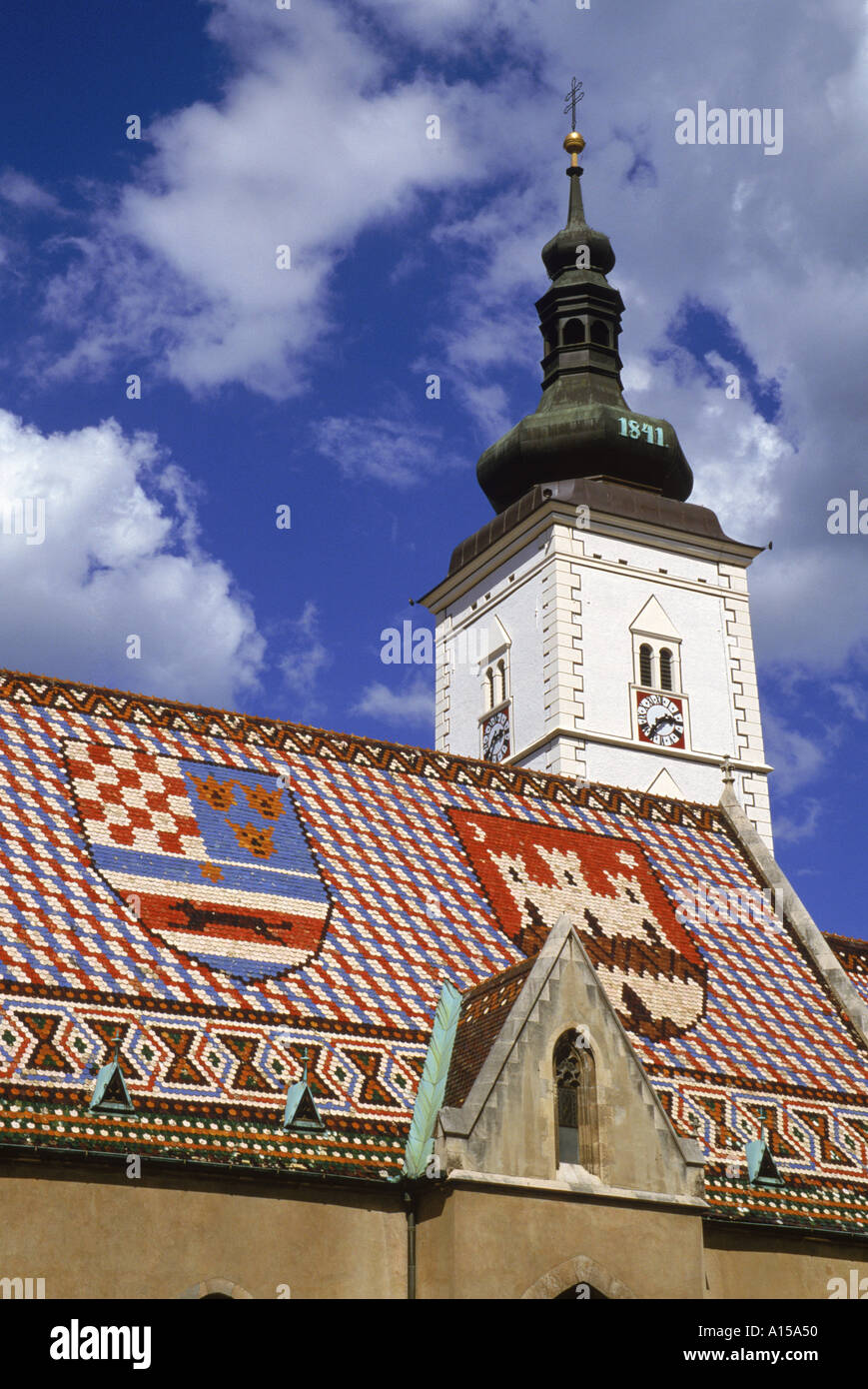 Close up of tile roof with pattern of shields and clock tower of St Marks church Zagreb Croatia K Gillham - Stock Image