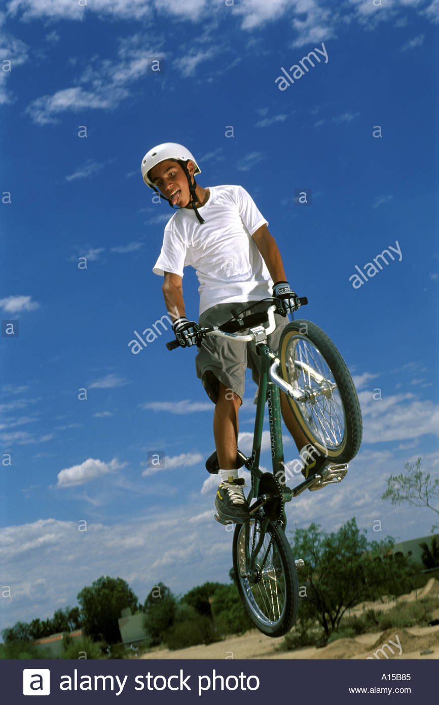 Mexican American Teenage teen Male BMX bicycle Jump with Tounge hanging out  with style. Model Released - Stock Image
