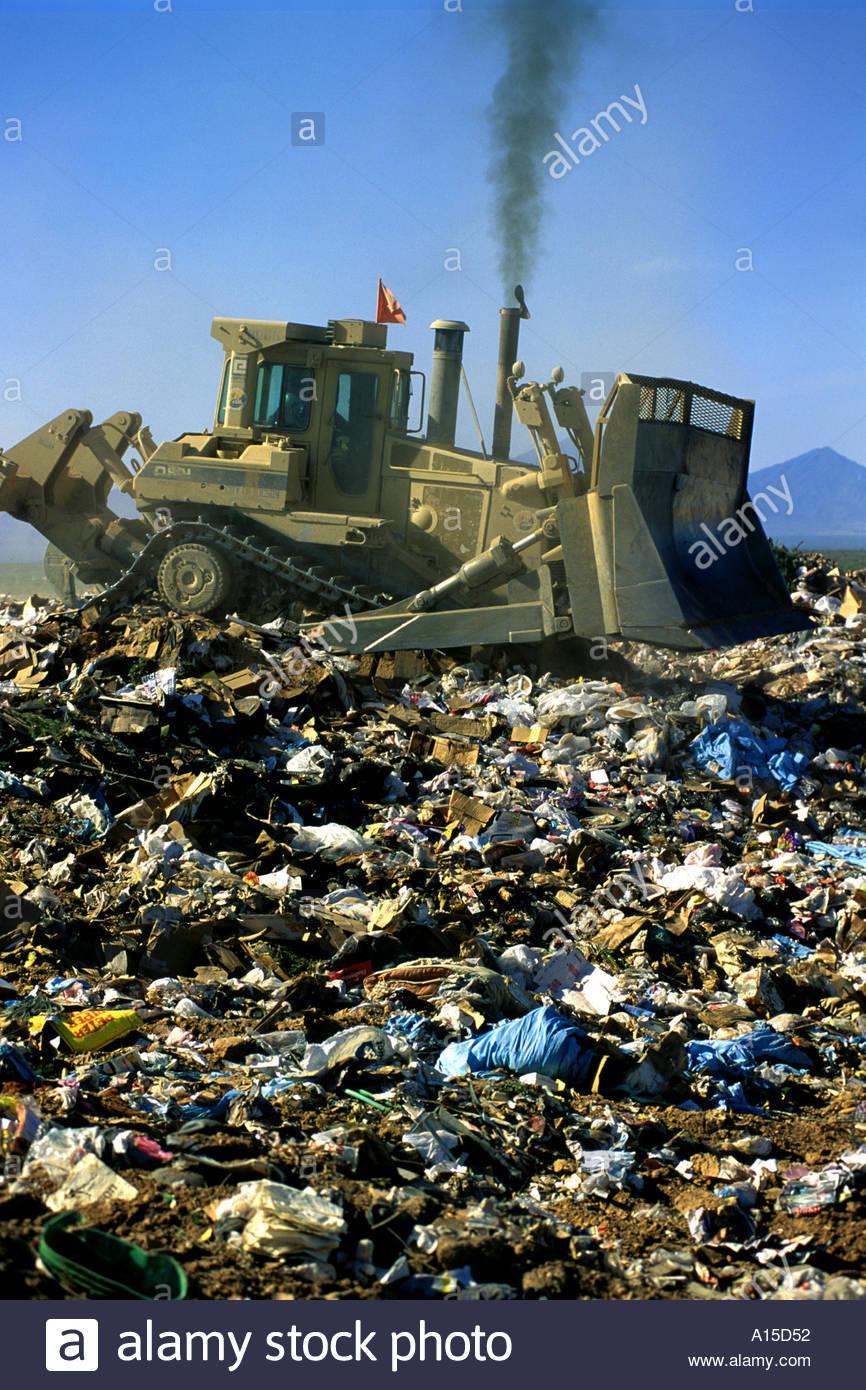Bulldozer pushing garbage at landfill dump side view - Stock Image