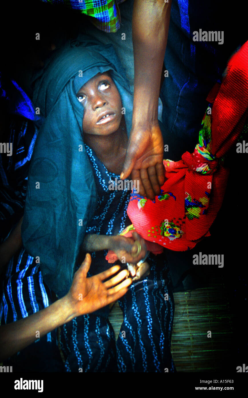A young girl who has recently been circumcised receives money by an elder during a celebration for all the newly - Stock Image