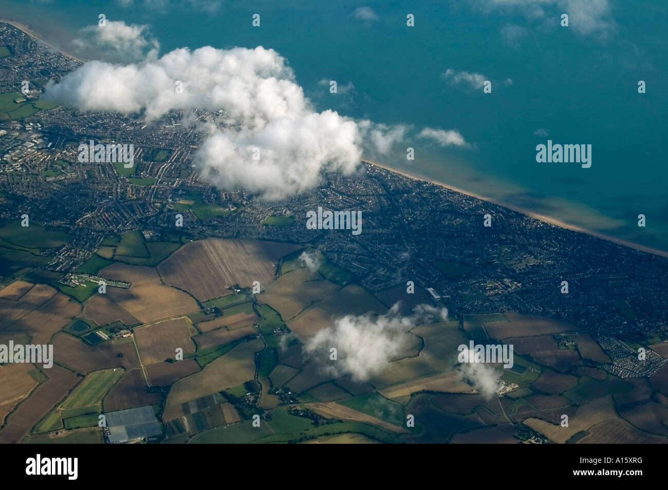 Horizontal aerial bird's eye view from an aeroplane of the patterned countryside and Sussex coastline on a clear - Stock Image