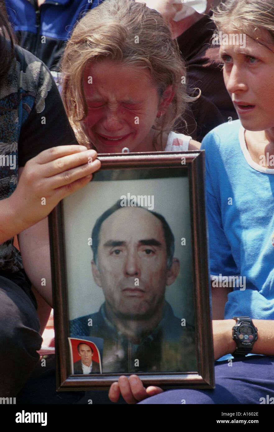 A Kosovar Albanian mourns her fathers' death Sunday July 25 1999 in Ljubenica Kosovo during a memorial service for Stock Photo