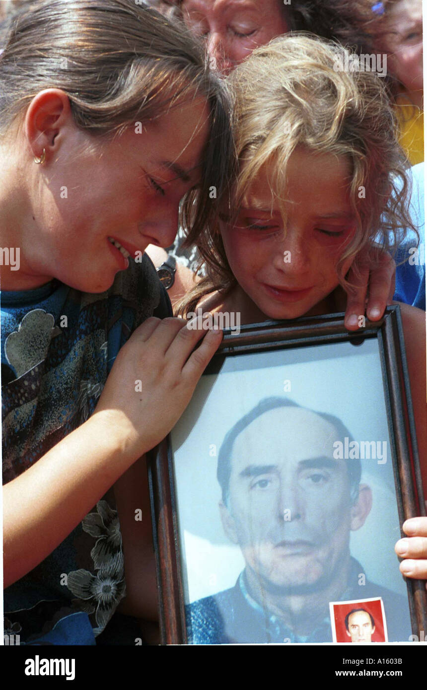 Kosovar Albanians mourn their fathers' death Sunday July 25 1999 in Ljubenica Kosovo during a memorial service for Stock Photo