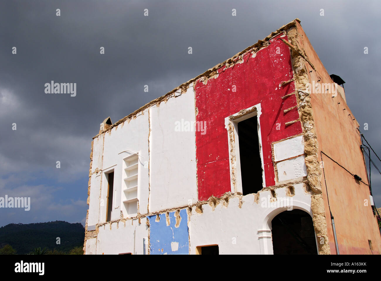 'Remaining half of demolished house against stormy sky, ^Mallorca'. - Stock Image
