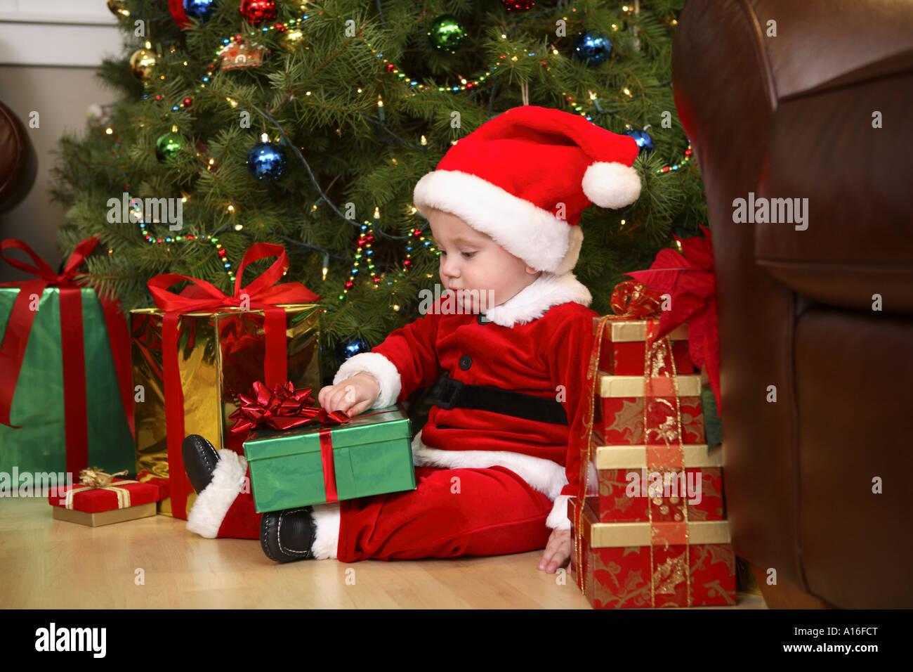 One year old boy dressed like Santa opening presents Stock Photo ...