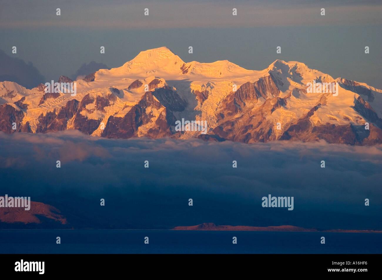 Sunset over mounts Illampu 6368 mt and Ancohuma 6427 mt Isla del Sol Lake Titicaca Bolivia - Stock Image