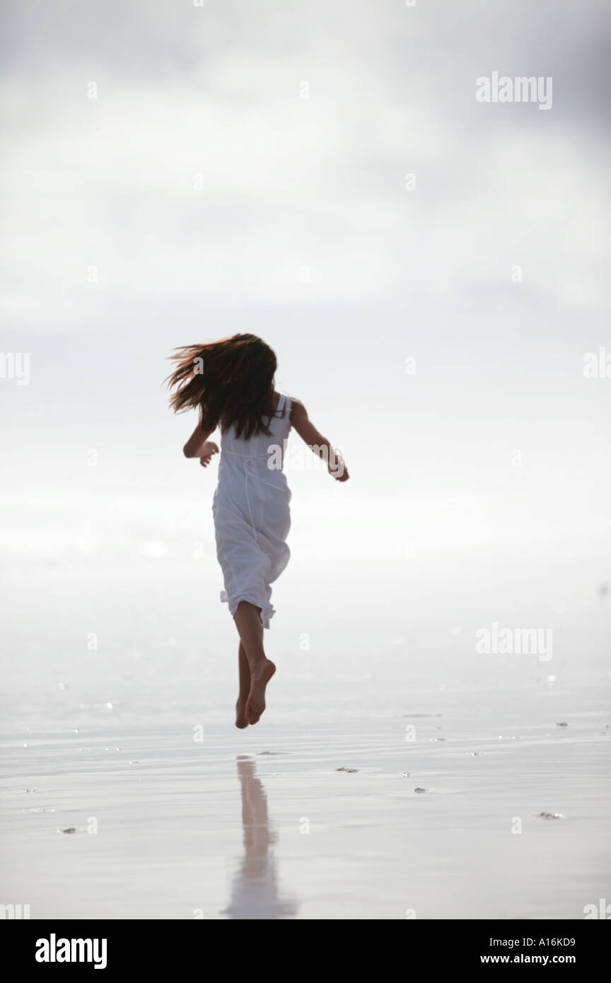 Woman 18-19, 20-24, 25-29, Years Old, in white dress running on beach (rear view) Stock Photo