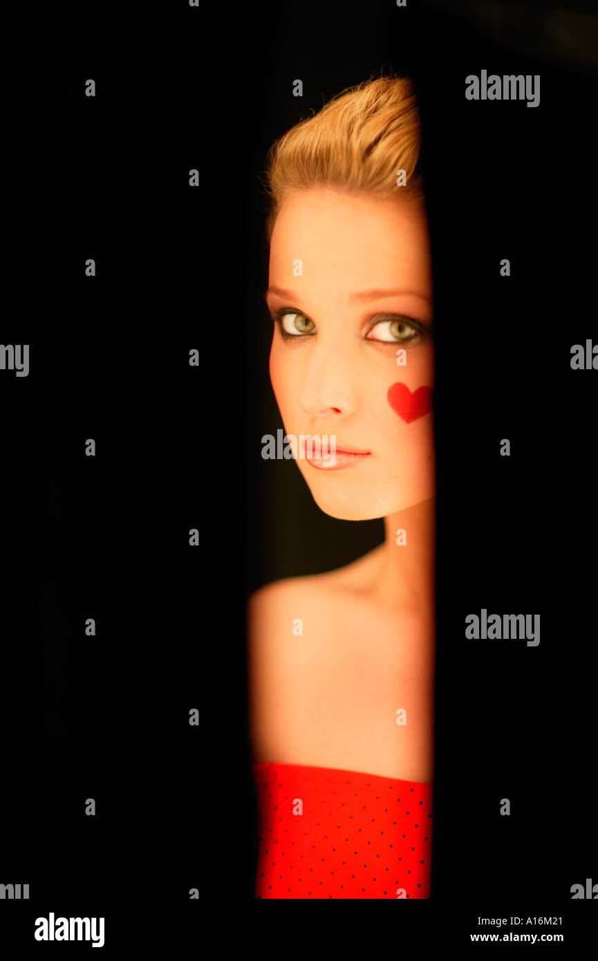 Portrait of young woman 18, 19, 20-24, 24-29, 30-34, years old with red heart painted on her cheek - Stock Image