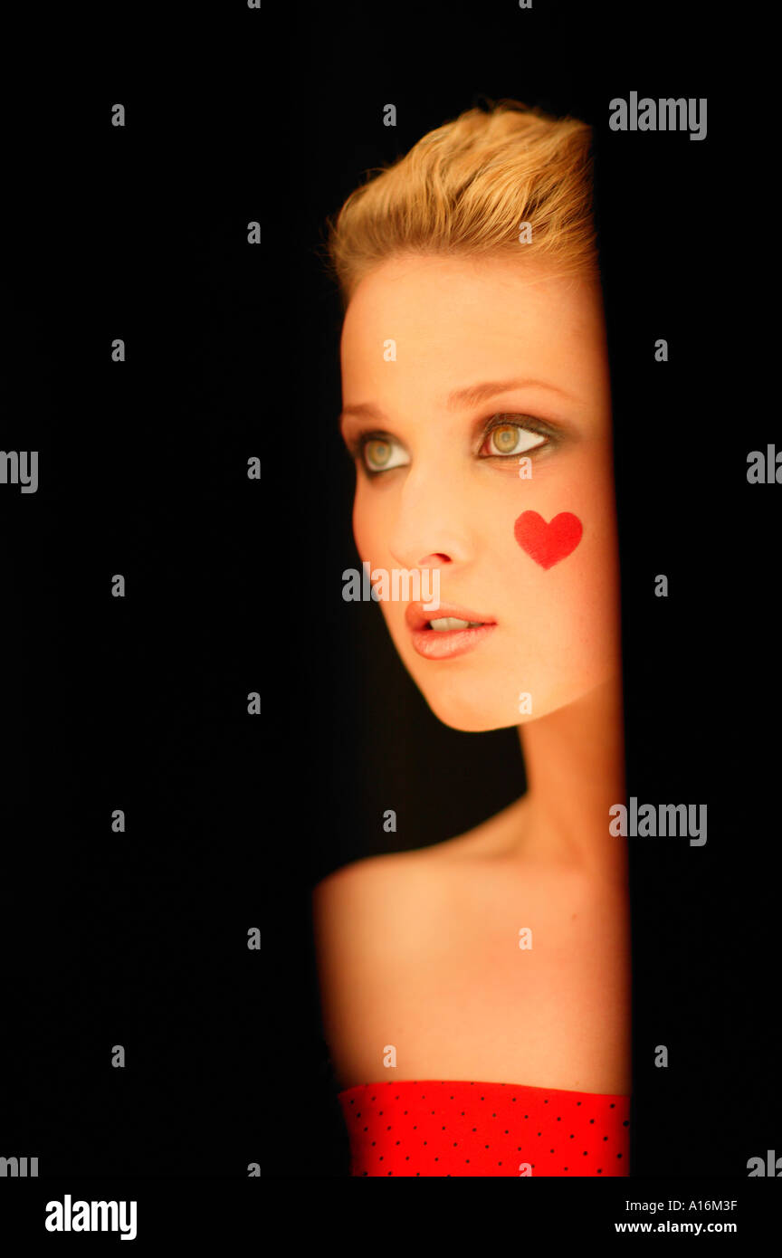 Portrait of young woman 20-24, 24-29, 30-34, years old with red heart painted on her cheek - Stock Image