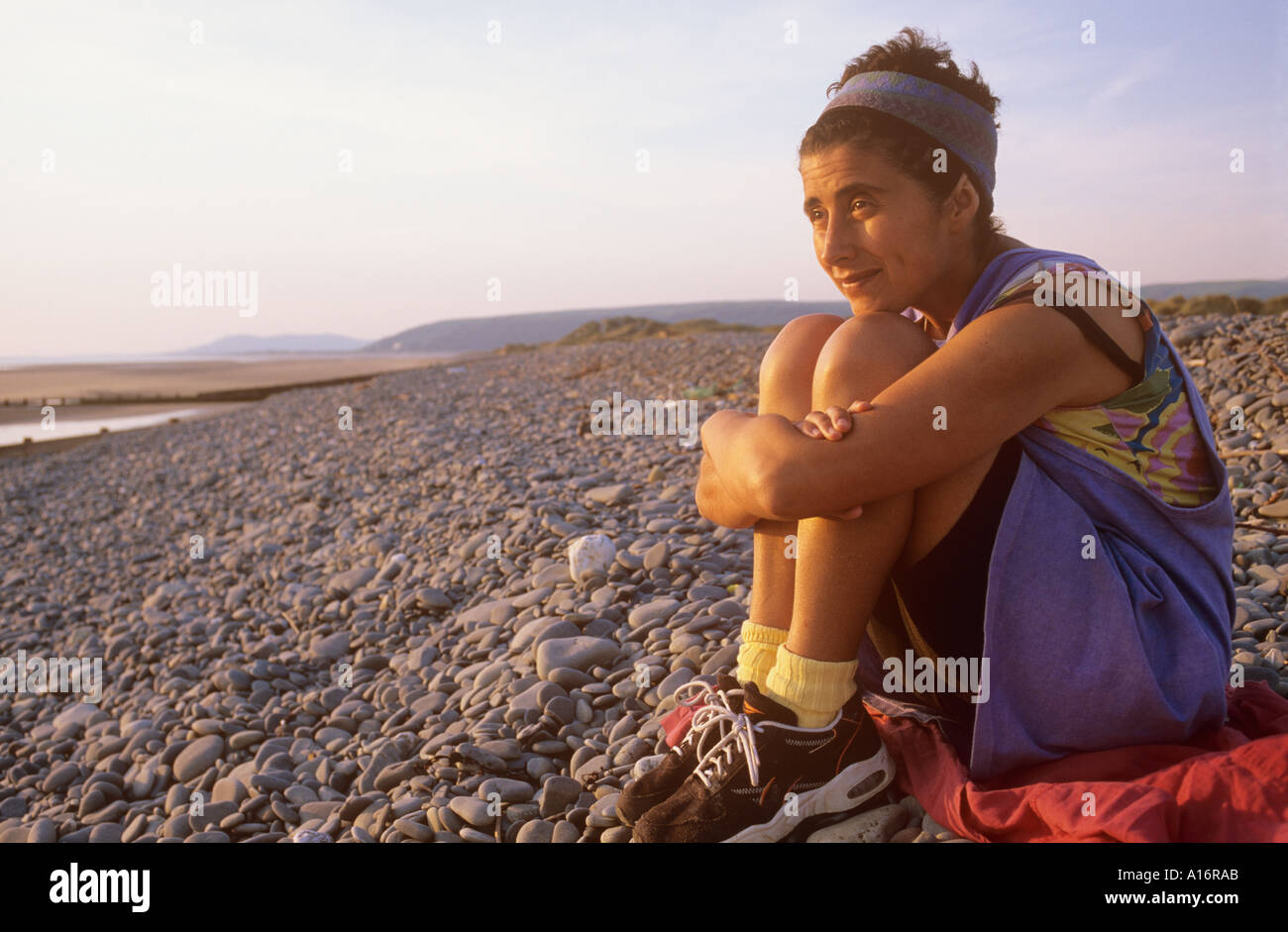 Woman on beach in evening sun - Stock Image