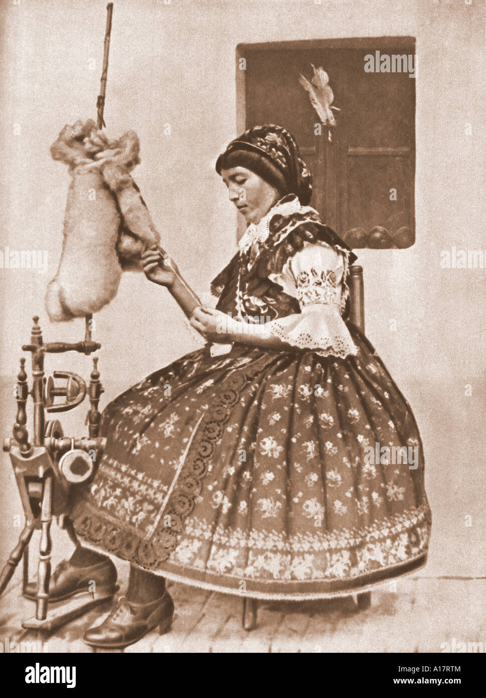Historical Photograph of Magyar Woman at Spinning Wheel in Traditional Dress - Stock Image