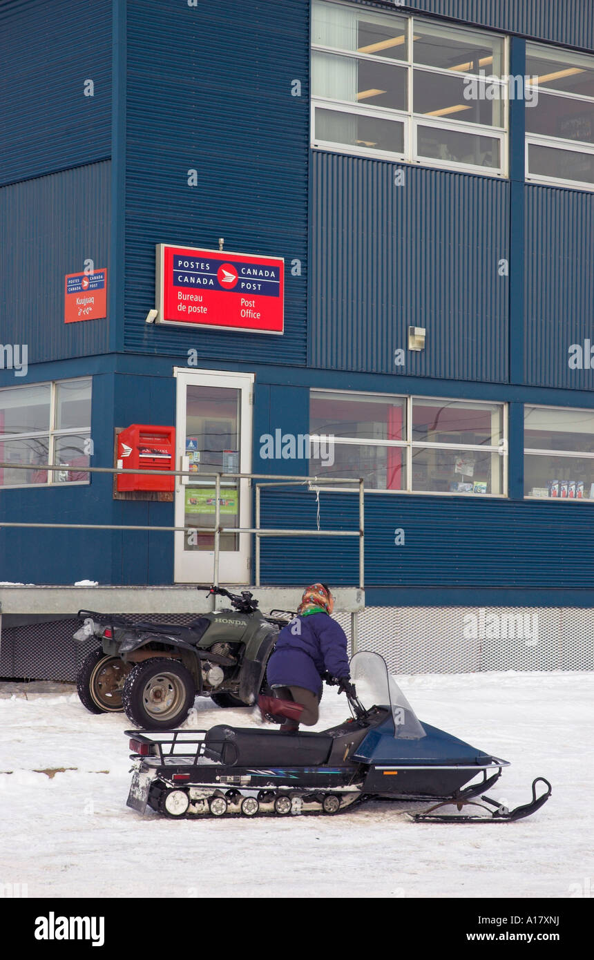 An inuit woman getting onto her snowmobile outside the post office in the arctic village of Kuujjuaq - Stock Image
