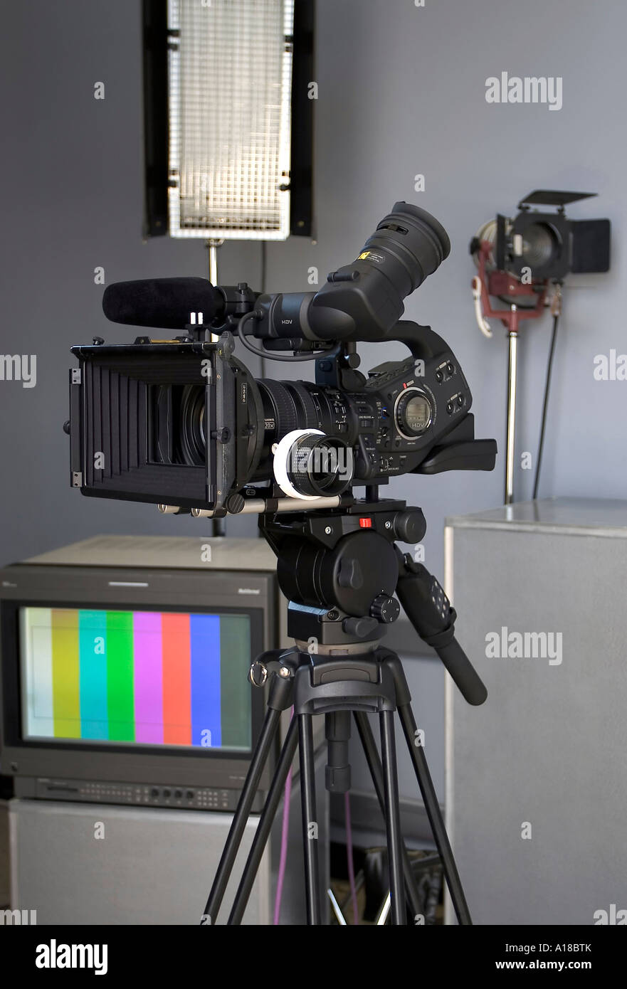 High Definition Video Camera in a Studio Setting with Professional Lighting and a Broadcast Television Monitor in the Background & High Definition Video Camera in a Studio Setting with Professional ...