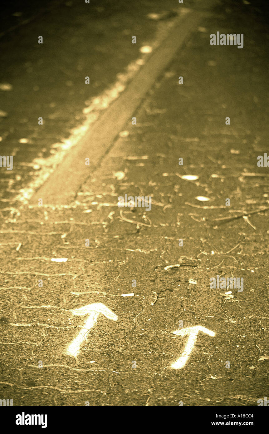 Two arrows painted on sidewalk - Stock Image