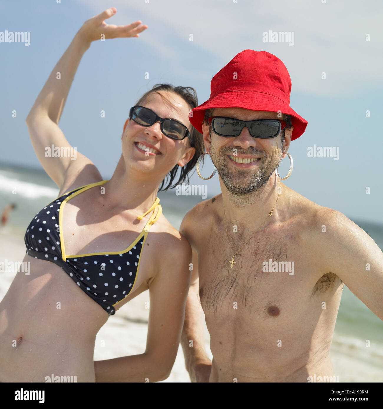 Father and daughter posing for the camera at the beach - Stock Image