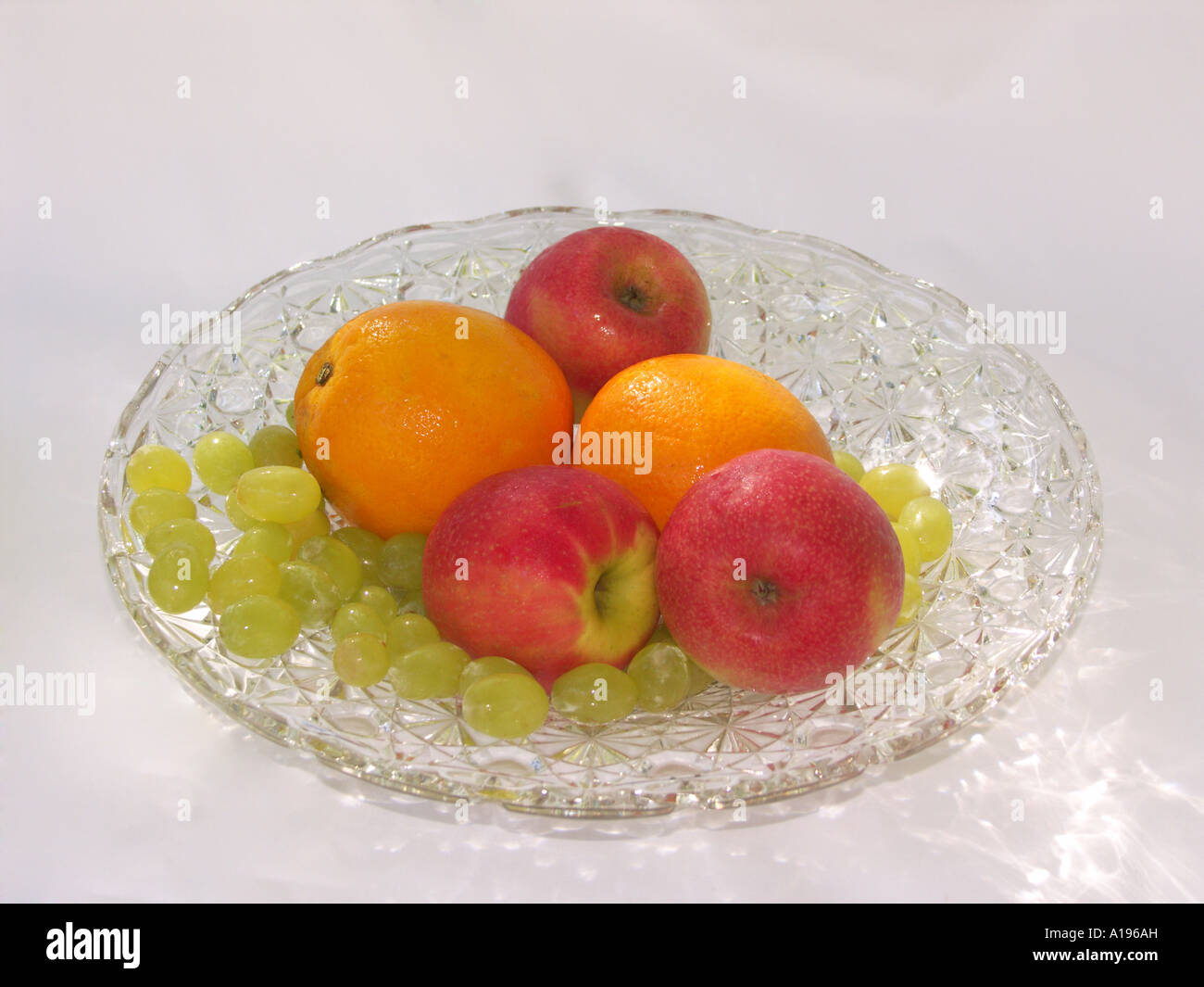 Crystal glass bowl plate with selection of fresh fruit, apples, oranges, and grapes, on a plain white background - Stock Image