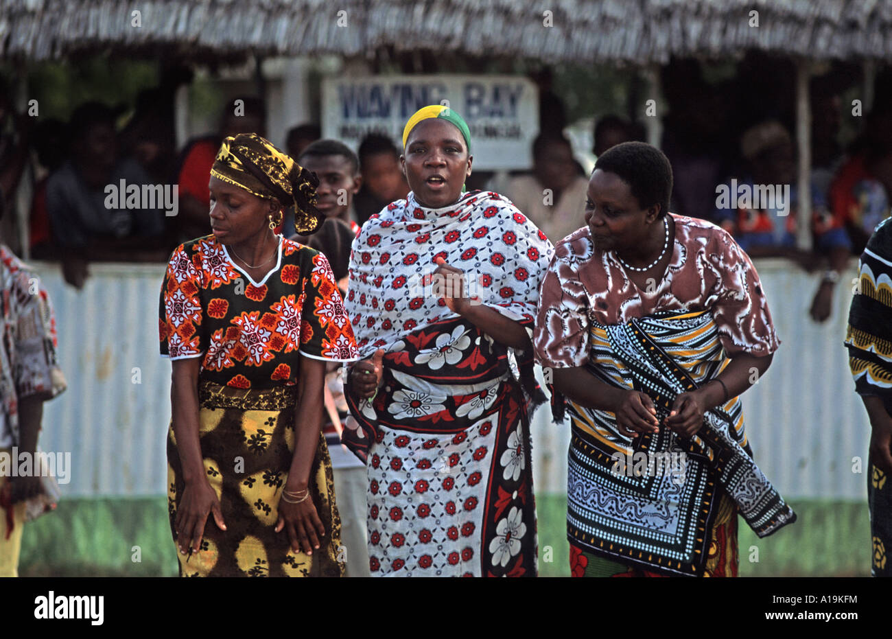 Group of women greeting a VIP arrival at Kilindoni arport Mafia island Dancing clapping and singing in celebration - Stock Image