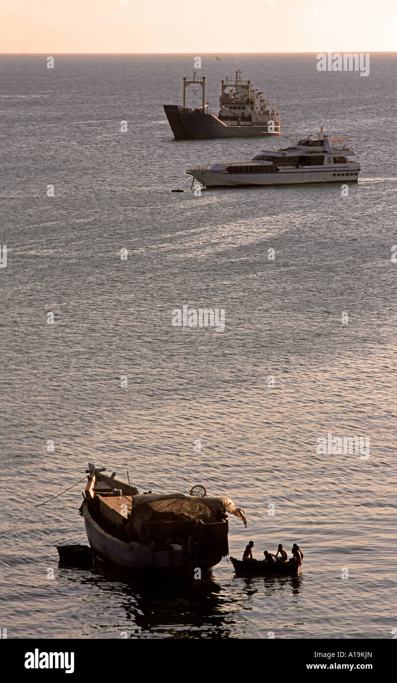 Silhouetted boats in Stone Town harbour in the late afternoon Unguja Zanzibar Tanzania East Africa - Stock Image