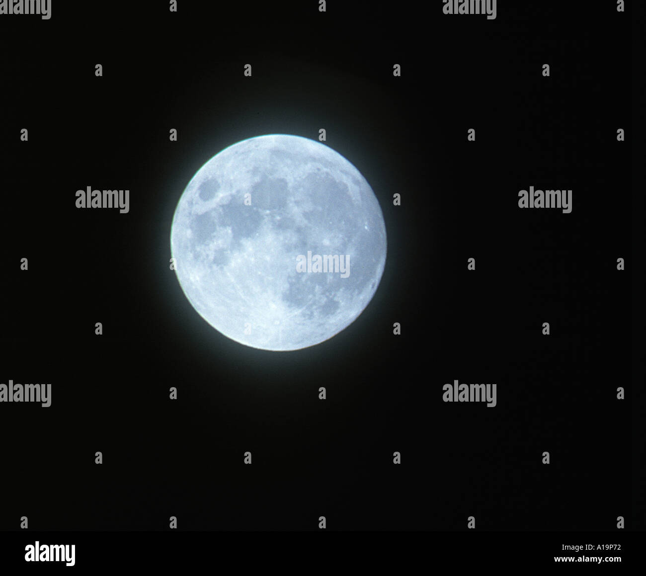 The moon with blue haze agianst a black sky - Stock Image